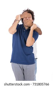 A young man is resisting someone's hands trying to control his sight and speech. Isolated on white background.