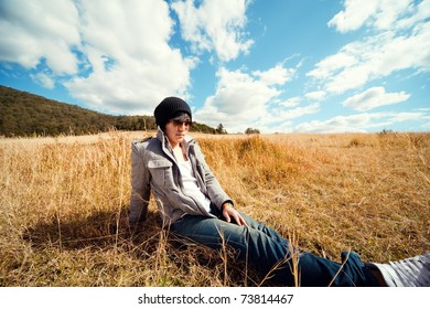 Young man rest on golden field.