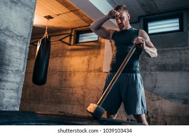 Young man resting after doing sledgehammer exercises at the gym