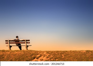 young man resting alone on a bench in an empty landscape at dusk