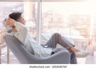 Young man resting in armchair. Joy of life