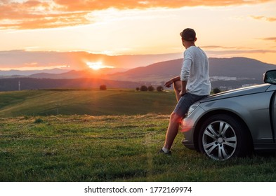 Young man resting during long solo auto trip sitting on his luxury car bonnet and enjoying the sunset sky colors. Traveling by car concept image.
