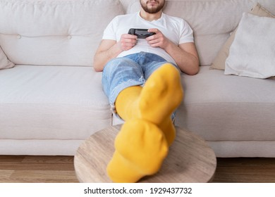 Young man resting, lying on sofa and playing video games.