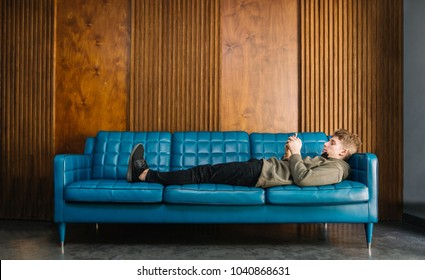 Young man resting on the couch and looking at the phone on a wooden background. The student lays on a blue sofa and uses a smartphone.