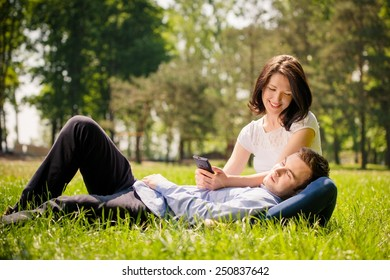 Young man is resting on woman's knees while she is playing with smartphone