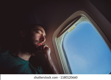 Young man resting and sleeping on an airplane.