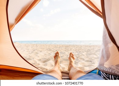 Young man resting in a tent on sand beach near the sea, point of view.