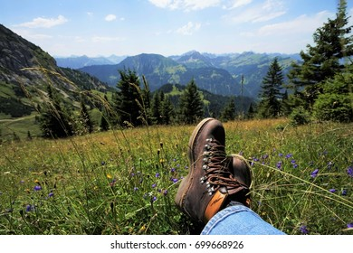 Young man resting in the Tyrolean Alps, you can see the mountain boots