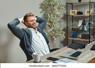 Young man resting from work on laptop holding hands behind head in home office