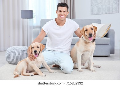 Young man resting with yellow retrievers at home