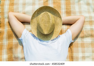 Young man rests and sleeps under straw hat on checkered plaid in nature
