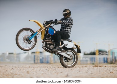 Young man is ridding on off road motorcycle in the desert and doing wheelie.