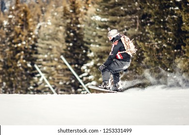 Young man rides snowboard and enjoying a frozen winter day on mountain slopes.