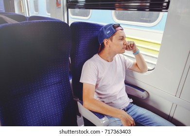 young man rides a train, looks out the window, travel, comfortable trip trip.