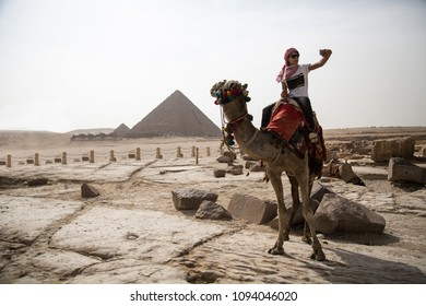 Young man riding the back of a standing camel raising his phone taking a selfie, the great pyramid in the background behind him.