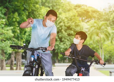 Young man riding a bicycle with his son and pointing out a place at the park while wearing face mask during new normal lifestyle