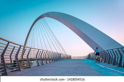 young man riding bicycle through Dubai water canal bridge famous Tourist attraction of Middle east amazing modern architecture Bridge, Dubai Travel and tourism concept image