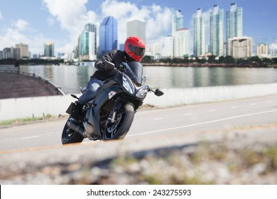 young man riding  big bike ,motorcycle on city road against urban and town building scene