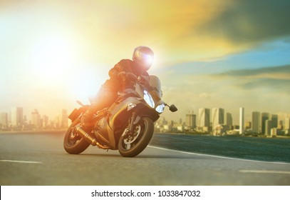 young man riding big motorcycle leaning on sharp curve with urban building background