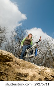 Young man riding bike, low angle view