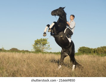 young man riding a black stallion in the nature