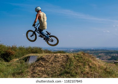 Young man riding bmx bike and jumping  on the hill