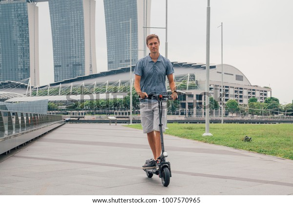Young man riding an electric scooter in Singapore with an amazing view on the city.