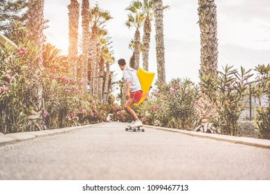 Young man riding longboard around city streets holding boogie surf board - Skater having fun going with skateboard - Youth lifestyle and millennial trend concept - Focus on his body