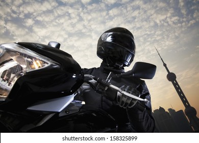 Young man riding a motorcycle during the day