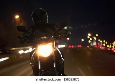 Young Man riding motorcycle at night