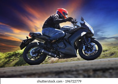 young man riding motorcycle on curve of asphalt  road against dusky sky use for people in leisure motor sport