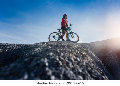 Young man riding mountain bike on the background of mountains at sunset