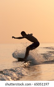 a young man riding on surf  on the waves at sunset