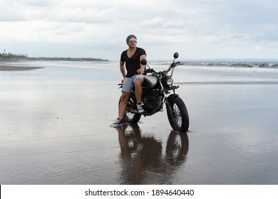 Young man riding a retro motorcycle on the beach, outdoors portrait, posing, in sunglasses, shorts, sneakers and t-shirts, travel together, ocean, sea