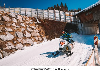 Young man riding a snowmobile on a track in the middle of the Austrian Alps