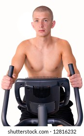 Young man riding a stationary bike in the gym