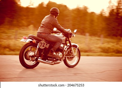 Young man riding a vintage motorcycle converted to a cafe racer. Fake license plate number. Short depth of field. Camera panning for motion blur.