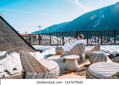 Young man in a robe chilling on a open terrace in the SPA with an amazing mountains view during winter time. Ski resort.