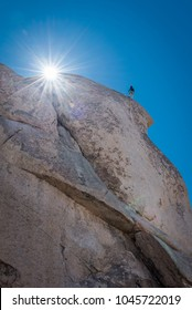 Young man rock climbing at Joshua Tree National Park in California