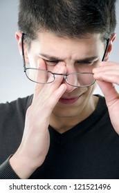 Young man rubs his eyes - eyesight problem concept