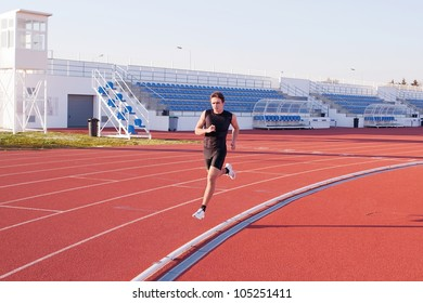 A young man run jogging in the stadium.