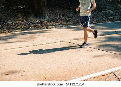 young man runner athlete running at road in a park