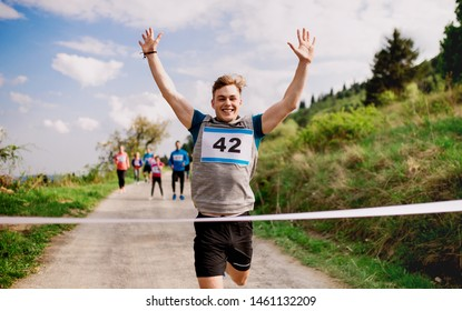 Young man runner crossing finish line in a race competition in nature.