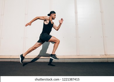Young man runner running along wall with copy space. Sport, fitness, jogging