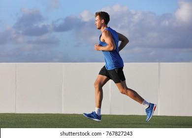 Young man runner running in city park on summer grass outdoors at sunset at outdoor stadium fitness centre. Healthy lifestyle.