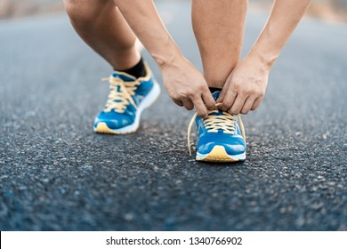 Young man runner tying shoelaces on road in outdoors.