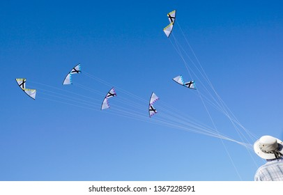 A young man is runnig a kite on tne beach of Pacific ocean