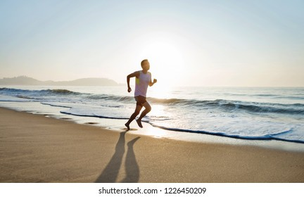 Young man running along beach  in the morning