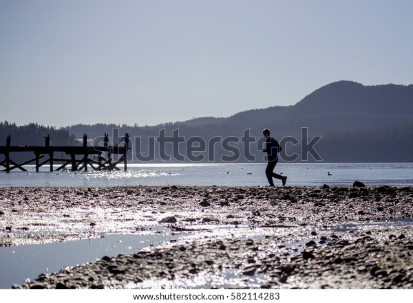 young man running along the rocky ocean beach with a wooden dock in the background on a bright sunny day.
