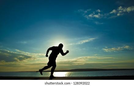 Young man running along the seashore at sunset